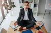 calm-peaceful-young-man-meditating-table-meeting-room_152404-6873